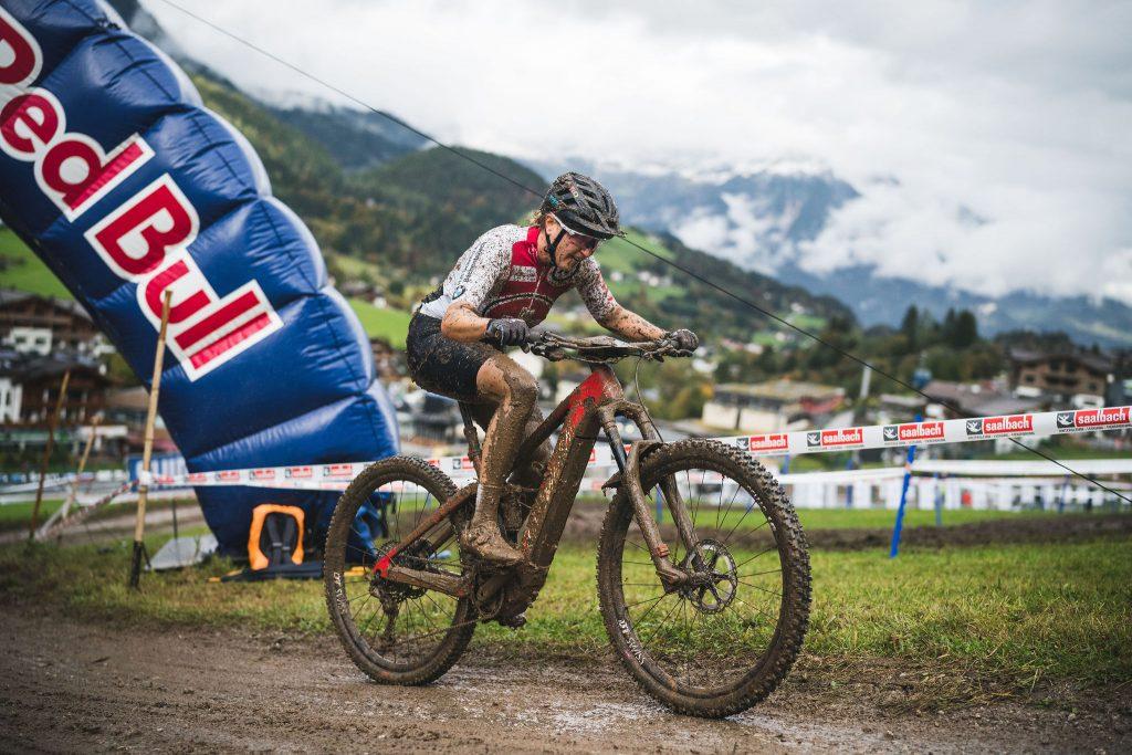Nathalie Schneitter aus der Schweiz fährt voller Schlamm und völiig außer Atem durch den Red Bull Torbogen Terrain der UCI Downhill WM Leogang mit völligst verschlammter Kleidung