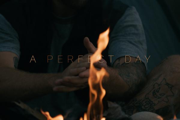 Tomas Lemoine sitzt mit reibendem Händen vor dem Lagerfeuer. Auf seiner Haut sind seine zahlreichen Tattoos zu sehen