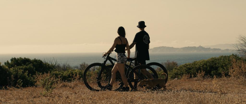 Tomas Lemoine, seine Freundin Carla & ihr Hund Rolly schauen auf das offene Meer mit ihren beiden Bikes in der Hand