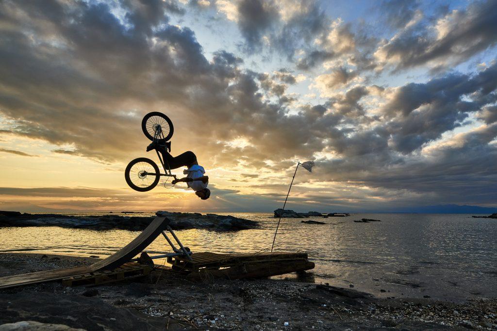 Tomomi macht während eines atemberaubenden Sonnenuntergangs einen Backflip am Strand Richtung Meer