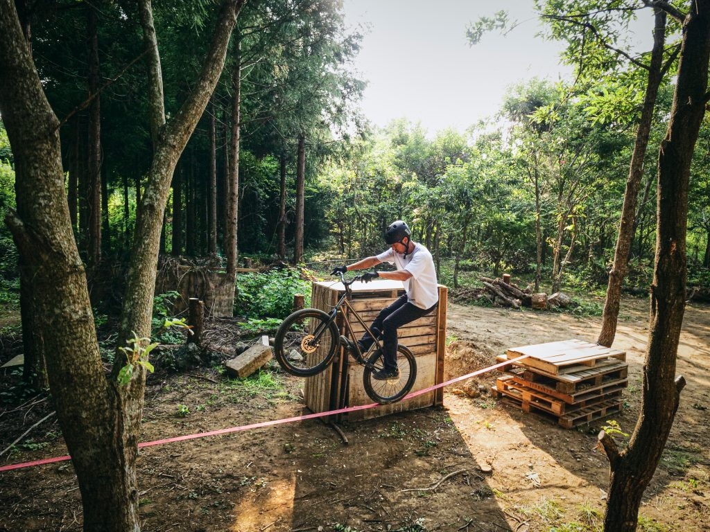 Tomomi macht einen Wheelie auf einer Slackline im Wald