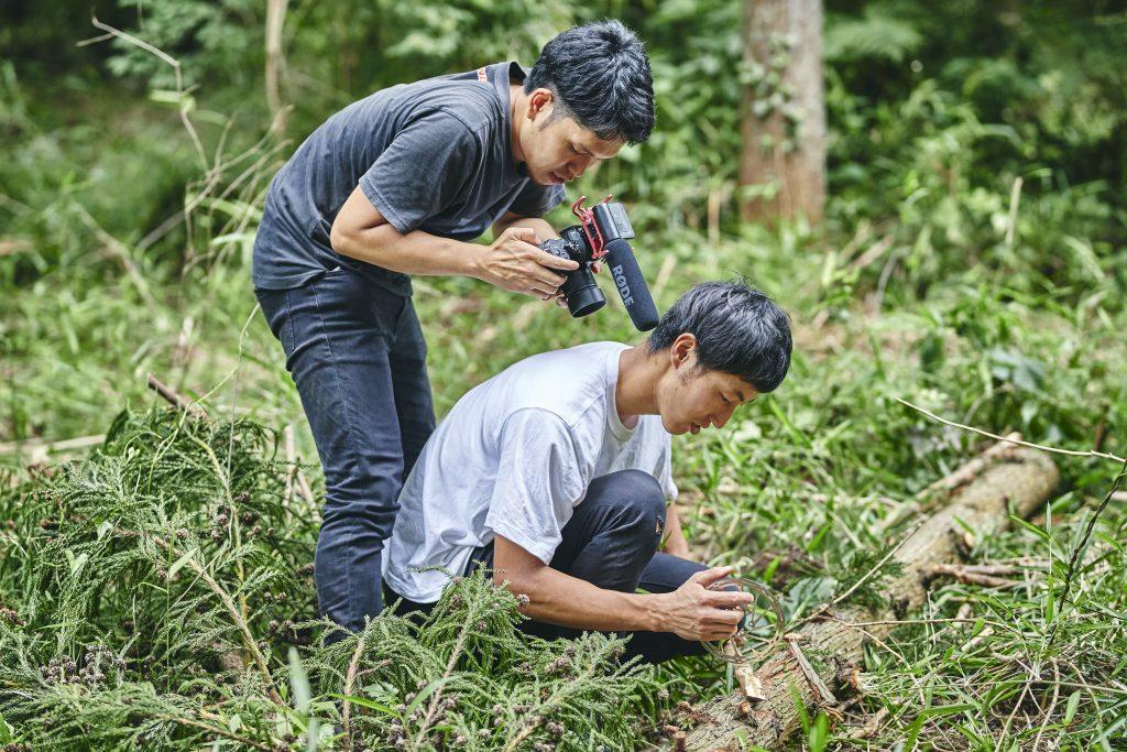 Tomomi wird von seinem Fotografen gefilmt, wie er mit einer Scheibenbremse einen Baumstamm schnitzt