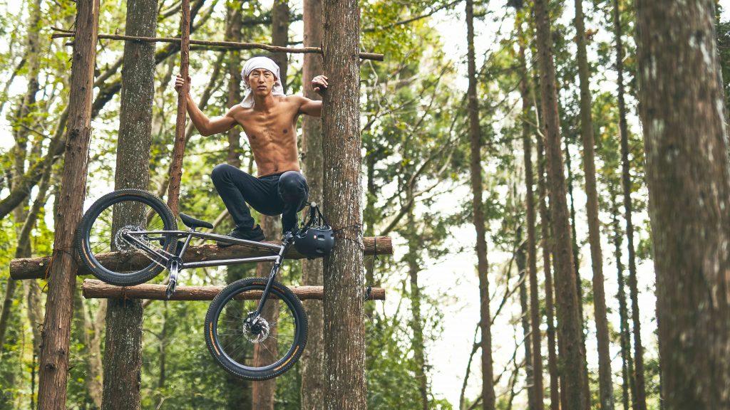 Tomomi hockt oberkörperfrei in den Baumkronen mit seinem Bike